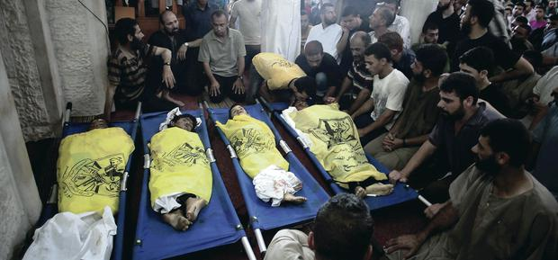 Mourners surround the bodies of the boys after the deadly strike