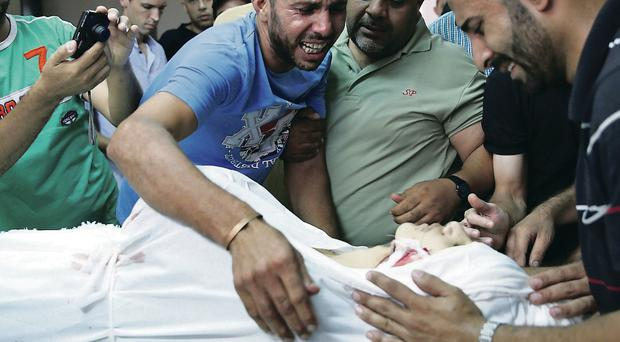 Relatives with the body of a member of the Abu Tawela family, killed in an Israeli air strike