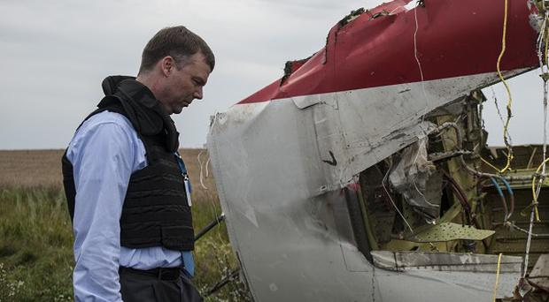 Alexander Hug, deputy head of the OSCE mission, inspects debris at the crash site (AP)