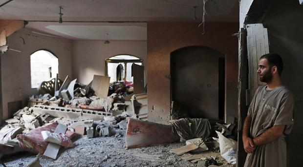 A Palestinian inspects the damage at an apartment destroyed by an Israeli strike in Beit Lahiya (AP)