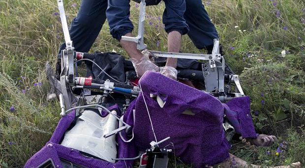 An emergency worker cuts through aircraft seat belts to free the body of a victim at the crash site (AP)