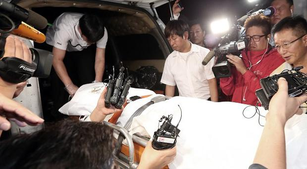The body of the fugitive owner of the sunken ferry Sewol is carried into an ambulance in Suncheon, South Korea (AP)