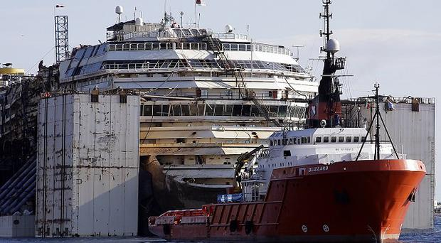 The wreck of the Costa Concordia is manoeuvred into position to be towed to the Italian port of Genoa, where it will be scrapped (AP Photo/Gregorio Borgia)