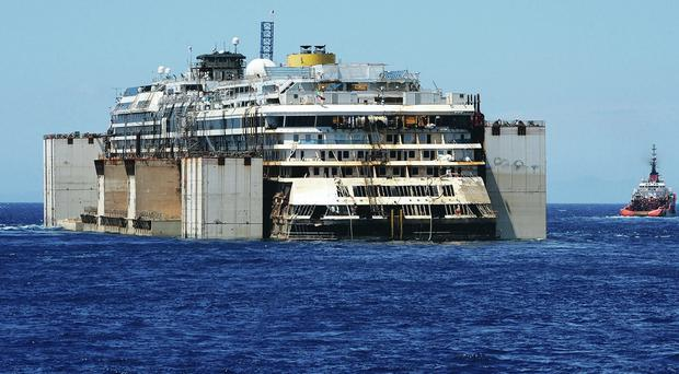The wreck of cruise liner Costa Concordia is towed by tugs from Giglio into the open sea after being refloated yesterday