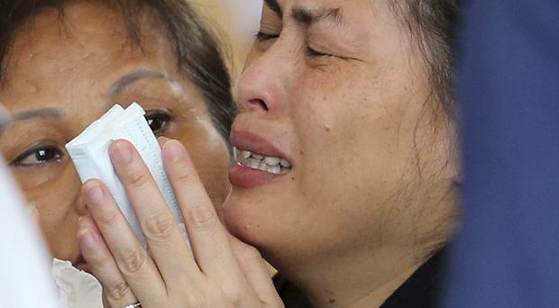 A relative of a passenger onboard the crashed TransAsia Airways Flight GE222 cries at a funeral parlour in Penghu
