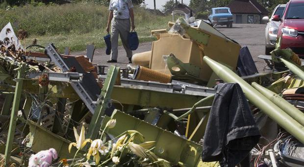 A man walks past wreckage of the crashed Malaysia Airlines Flight 17 in the village of Petropavlivka, eastern Ukraine (AP)