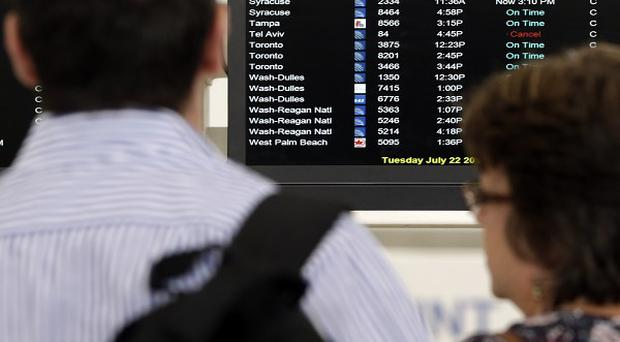 Travellers in front of a departures board showing a cancelled flight to Tel Aviv at Newark Liberty International Airport, New Jersey (AP)