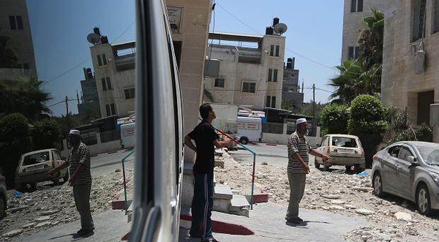 Palestinians check the damage at the Aqsa martyrs hospital, which was hit by an Israeli strike (AP)