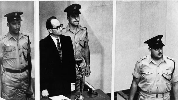 Adolf Eichmann standing in his glass cage in the Jerusalem courtroom where he was tried for war crimes committed during the Second World War (AP)