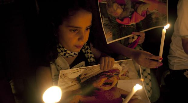 A girl holds a candle and a poster with a picture of an injured Palestinian child during a protest in the West Bank city of Ramallah (AP)