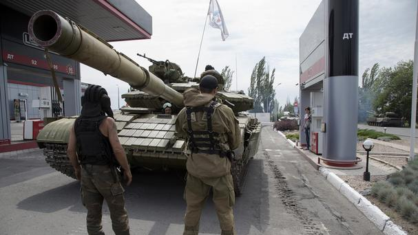 Donetsk People's Republic fighters fill their tank with fuel at a petrol station in Snizhne, eastern Ukraine (AP)