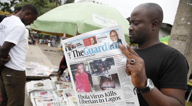 A man in Lagos reads a local newspaper with the headline Ebola Virus kills Liberian in Lagos (AP)