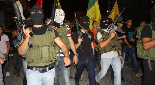 Masked Palestinian militants of Al-Aqsa Martyrs Brigades, march during a demonstration against the Israeli military action in Gaza (AP)