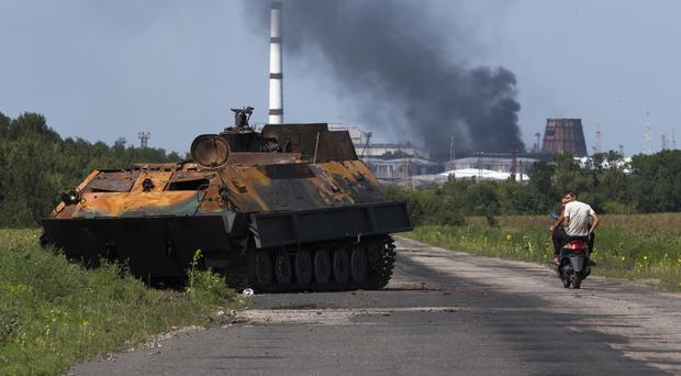 People ride a scooter past a destroyed pro-Russian fighters' APC in eastern Ukraine (AP)