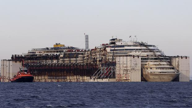 The wreck of the Costa Concordia cruise ship is towed by tugboats towards Genoa's harbour, Italy (AP)