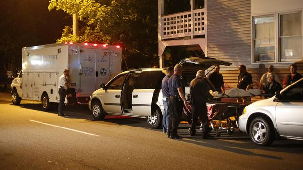 A body is moved from an apartment complex where five members of a family were found dead (AP)
