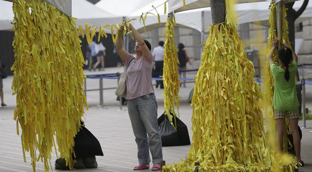 A mother and her daughter tie yellow ribbons with messages for missing passengers and victims aboard the sunken ferry Sewol (AP)