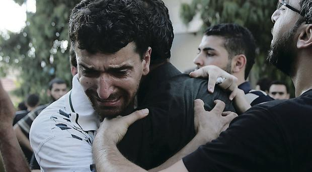 Palestinian relatives comfort each other at the morgue of Shifa hospital following an explosion that killed 10 people, nine of them children at a park at Shati refugee camp