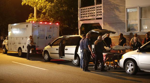 A body is moved from the flats where five members of a family were found dead (AP)