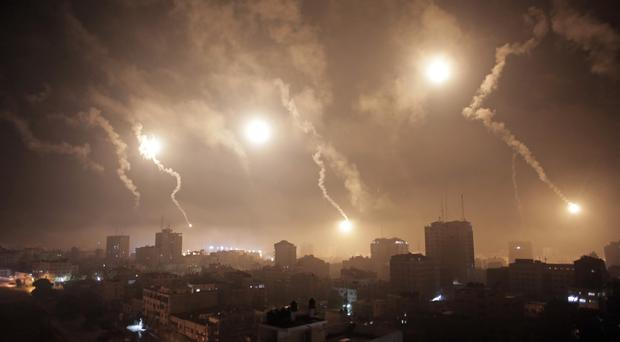 Israeli forces' flares light up the night sky of Gaza City (AP Photo/Khalil Hamra)