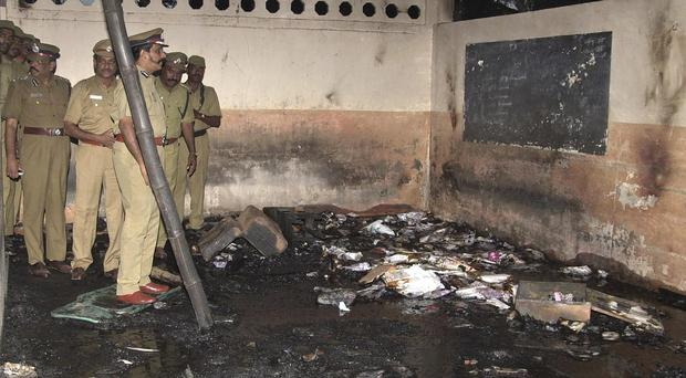 Indian police officers inspect the burnt remains of the school building in Kumbakonam. (AP)