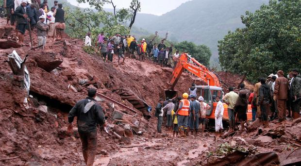 Rescuers work at the site of a landslide in Malin village, in the western Indian state of Maharashtra. (AP Photo/Nitin Lawate)