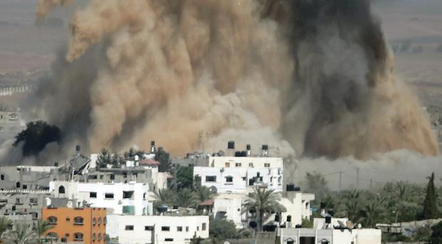 Smoke and sand from an explosion rise after an Israeli strike in Gaza yesterday