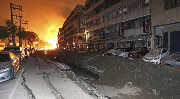 Vehicles line a destroyed street as flames continue to burn from multiple explosions from an underground gas leak in Kaohsiung (AP)