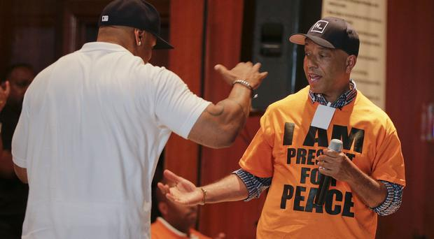 Actor and music artist LL Cool J, left, with Russell Simmons at the juvenile detention centre of Rikers Island jail (AP)