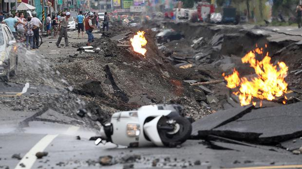 Vehicles lie on a destroyed street still burning following multiple explosions from an underground gas leak in Kaohsiung, Taiwan (AP)