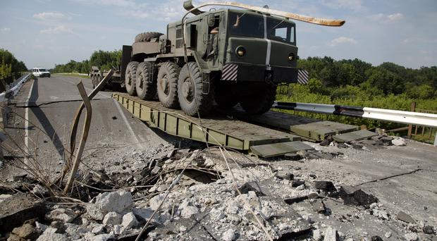 An Ukrainian government army military vehicle travels across a damaged bridge near the village of Debaltseve, Donetsk region, eastern Ukraine (AP)