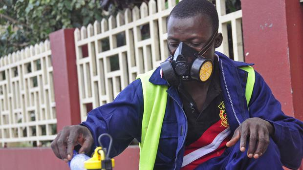 A Monrovia City Corporation worker mixes disinfectant before spraying it on the streets in a bid to prevent the spread of the deadly Ebola virus (AP)
