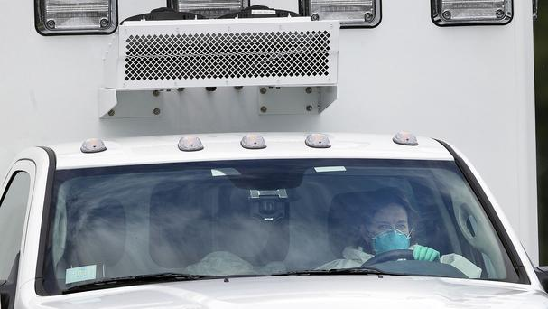 An ambulance driven by a woman in protective clothing carries Ebola victim Dr Kent Brantly to Emory University Hospital in Atlanta (AP)