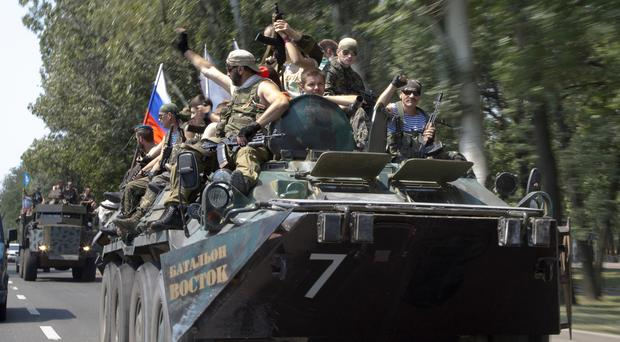 Pro-Russian rebels ride their armoured patrol car as they celebrate Paratroopers' Day in the city of Donetsk, eastern Ukraine on Saturday (AP)