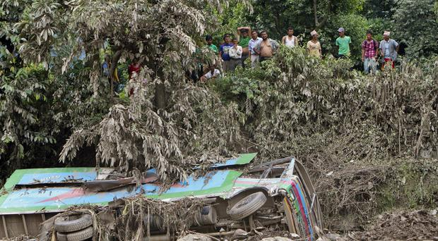 Local people watch a truck which was overturned by a landslide in Mankha village, about 120 kilometres (75 miles) east of Katmandu, Nepal (AP)