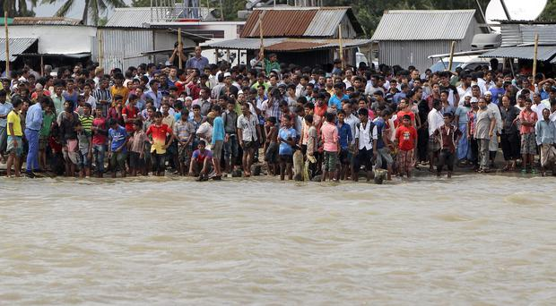 Bangladeshi people gather on the banks of the River Padma after a passenger ferry capsized in Munshiganj district (AP)