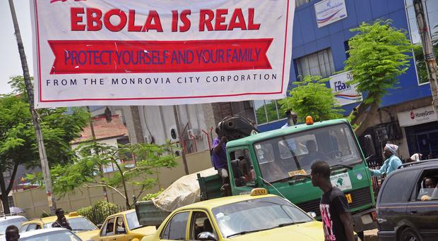 A banner reading 'Ebola is real, protect yourself and your family', warns people of the virus in Monrovia, Liberia (AP)