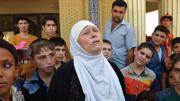 Displaced Iraqis wait for aid at a mosque on the outskirts of Irbil (AP)