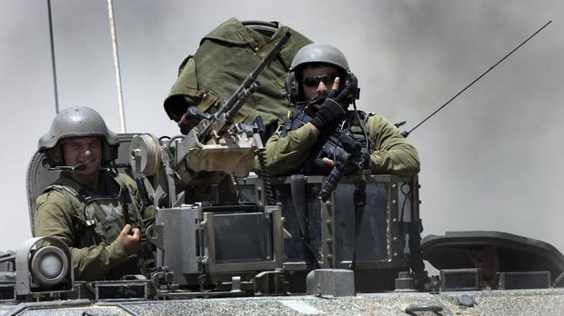 Israeli reserve soldiers on the top of an armoured personnel carrier returning to Israel from the Gaza Strip (AP)