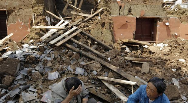 Villagers sit in front of their destroyed house following a massive earthquake in the town of Longtoushan in Ludian County in south-west China's Yunnan province (AP)