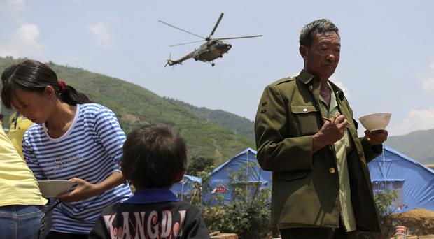 A helicopter flies past villagers receiving food from volunteers in Longtoushan following the earthquake (AP)