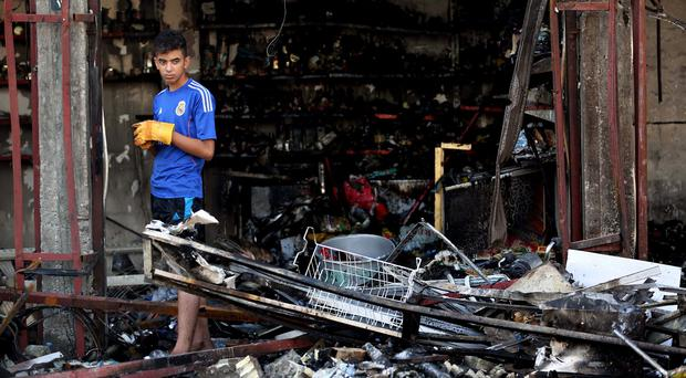 An Iraqi collects what he can from his destroyed shop after a string of car bombs tore through busy shopping streets in several areas of Baghdad (AP)