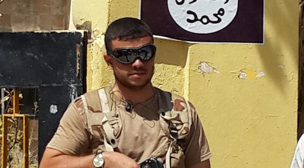 An Islamic State fighter stands guard at the headquarters of the Kurdistan Democratic Party in Bartella (AP)