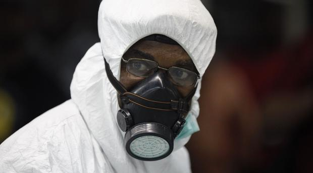 A Nigerian health official wears protective gear at the arrivals hall of an airport in Lagos (AP)