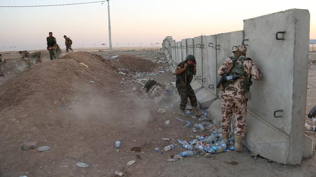 Kurdish Peshmerga fighters take cover during airstrikes targeting Islamic State militants near Irbil (AP)