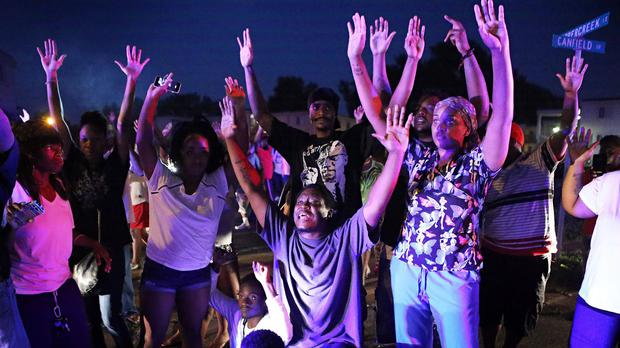 A crowd gathers near the scene where 18-year-old Michael Brown was fatally shot by police (AP)