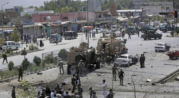 Nato and Afghanistan's security forces inspect at the site of a suicide attack in Kabul (AP)