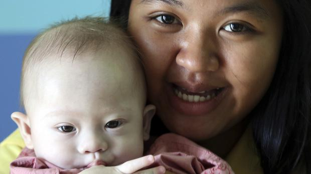 Thai surrogate mother Pattaramon Chanbua with the nine-month old boy who was born with Down's syndrome (AP)