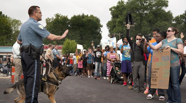Protesters confront police during an impromptu rally to protest against the shooting of Michael Brown (AP)