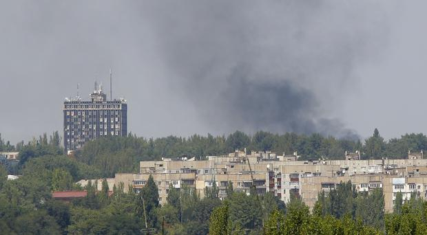 Smoke from shelling rises over a residential apartment houses in Donetsk (AP)